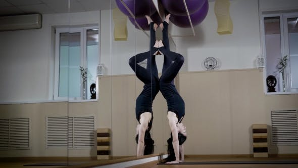 Thumbnail for Young Slim Woman Is Doing Headstand in a Gymnastic Hall, Leaning Against Wall Mirror, Symmetrical