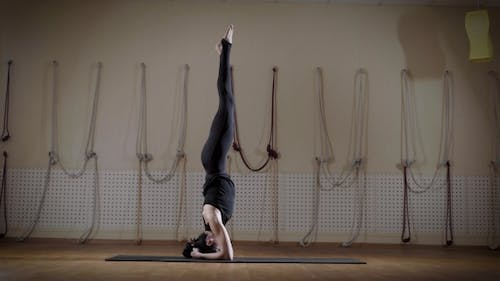Graceful Woman Is Doing Headstand in a Gymnasium and Changing Legs Poses, Doing Leg-split