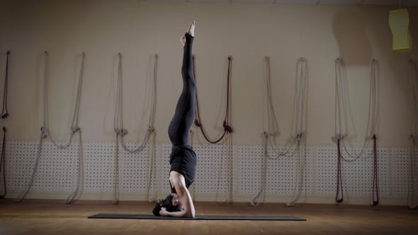 Thumbnail for Graceful Woman Is Doing Headstand in a Gymnasium and Changing Legs Poses, Doing Leg-split