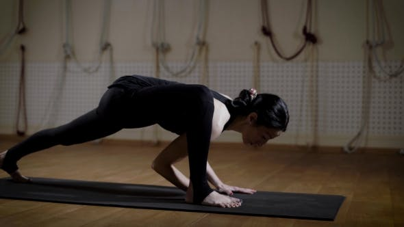 Thumbnail for Gymnast Woman Is Stretch Her Legs in a Fitness Room on a Floor Mat and Making Acrobatic Element