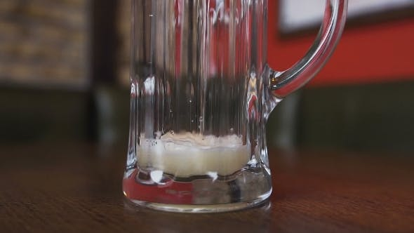 Thumbnail for On the Table There Is an Empty Glass in Which Pour Beer with a Foam Is Poured