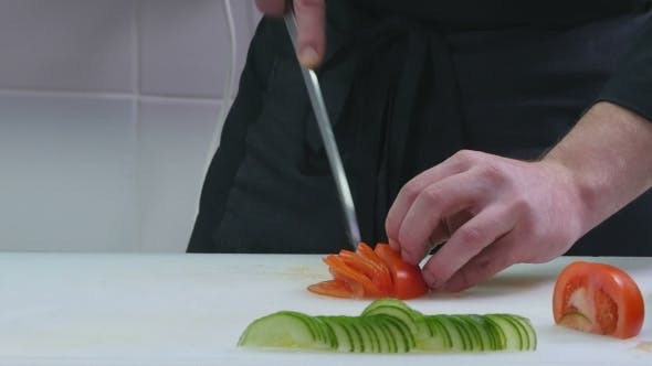 Thumbnail for Man in the Kitchen Cutting Tomato