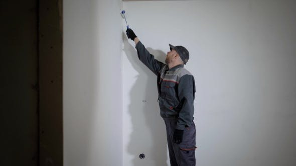 Working Man Is Priming Wall in Flat