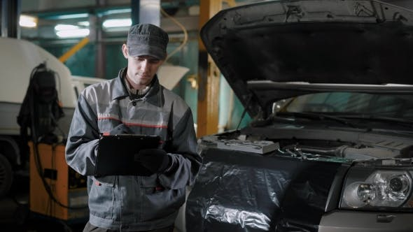 Thumbnail for Car Mechanic Is Standing in an Auto Repair Shop Near Automobile with Open Hood and Making Notes