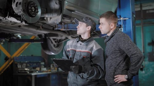 Automobile Mechanic Is Appraising a Brake Disk, Brake Pads and Hosepipe, Explaining for a Car Owner