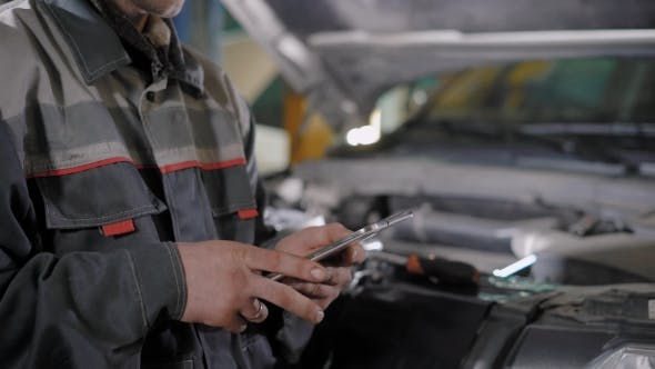 Thumbnail for Auto Mechanic Is Using Tablet for Calculating Value for a Car Repair