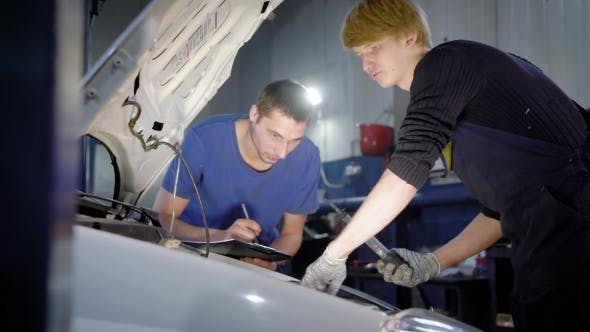 Thumbnail for Master Is Inspecting Inner Systems of Automobile in a Car Body Shop, Assistant Is Writing Results