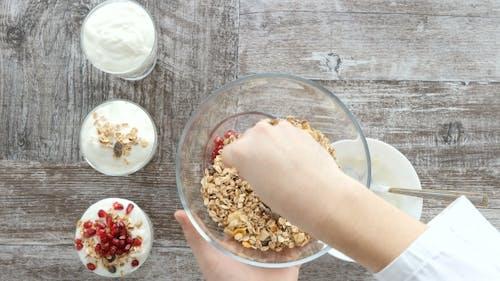 Chef Hands Preparing Muesli with Natural Yogurt and Pomegranate