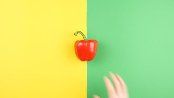 Thumbnail for Hand Placing Sweet Red Pepper on Two Colored Background