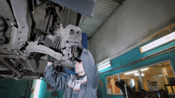 A Professional Repairman Checks the Maneuverability of the Wheels in Order for the Car