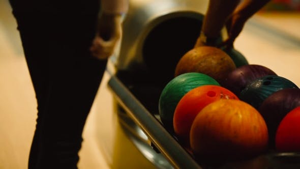 Thumbnail for The Girl Is Waiting for the Machine To Give Out Balls for Bowling