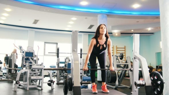 Cover Image for Black Hair Woman Exercising in Gym - Lifts Up the Weight
