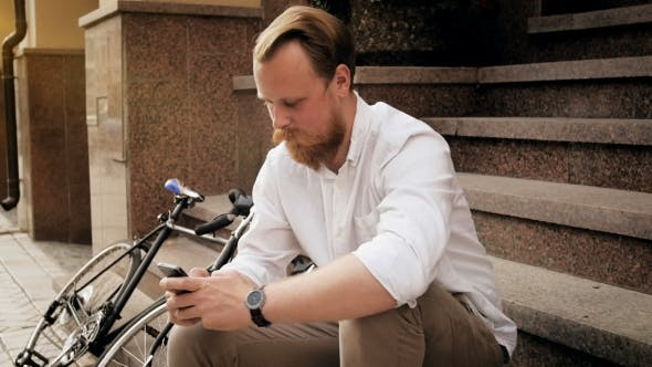 Thumbnail for Video of Handsome Bearded Man with Mobile Phone Sitting on Stairs on Street