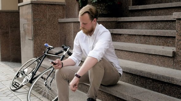 Thumbnail for Stylish Hipster Man Sitting on Staircase and Typing Message on Smart Phone