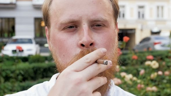 Thumbnail for Footage of Red Bearded Hipster Man Looking in Camera and Smoking Cigarette