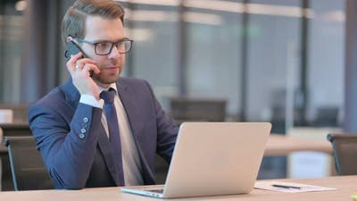 Businessman with Laptop Talking on Phone