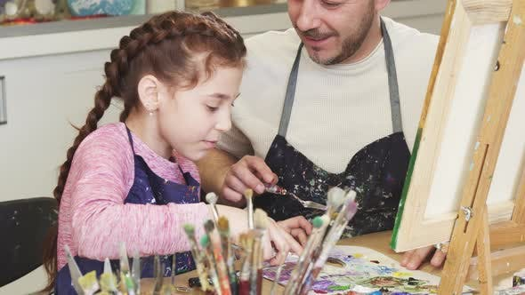 Thumbnail for Cropped Shot of a Cute Little Girl Smiling Talking To Her Dad Mixing Paints at Art Class
