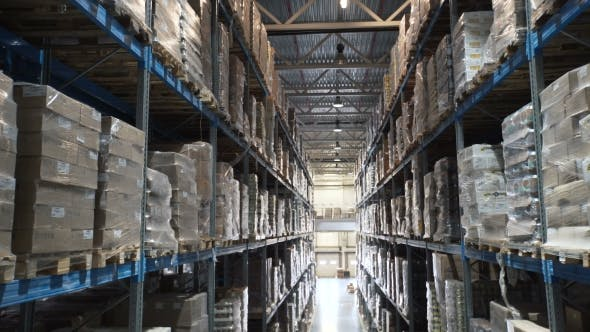 Cover Image for Camera Moves Up on Shelves of Cardboard Boxes Inside a Storage Warehouse