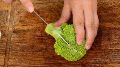 Hände, um Brokkoli in Scheiben zu schneiden