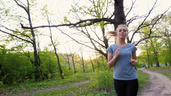 Cover Image for Beautiful Woman in T-shirt Makes a Run in the Spring Forest