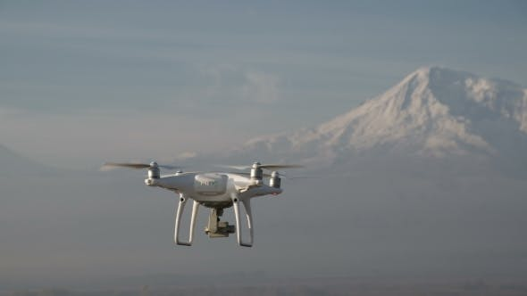 Thumbnail for The Quadcopter Is Flying High Above Snowy Mountain