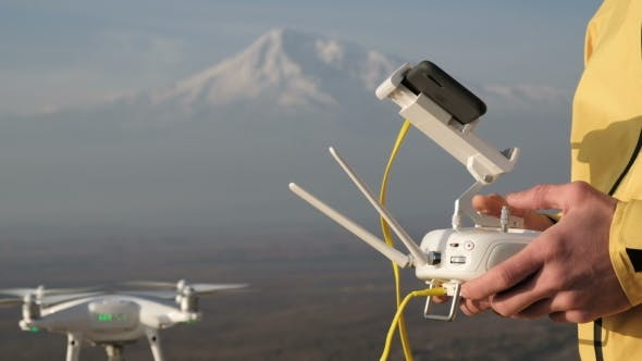 Thumbnail for Man Hands Control Flying Quadcopter near Mountain