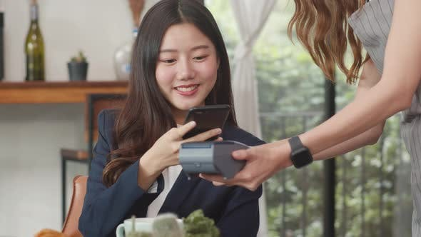 Asian business women pay contactless at coffee shop. Asian happy girl barista