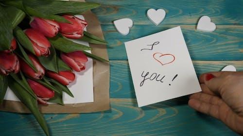 Ich liebe dich Nachricht Notiz und Tulpen Blumen Blumenstrauß auf einem Holztisch