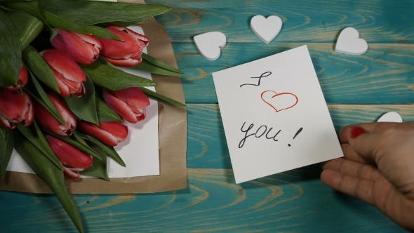 I Love You Message Note and Tulips Flowers Bouquet on a Wooden Table