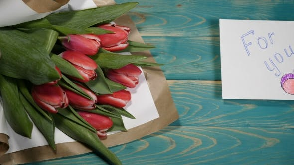 for You Message Note and Tulips Flowers Bouquet on a Wooden Table Couple Relationship