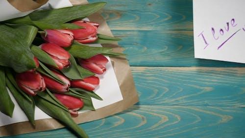 Ich liebe dich Nachricht Hinweis und Tulpen Blumen Blumenstrauß auf einem Holztisch Paar