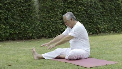 Asian Elderly woman pilates exercise in garden.