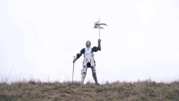 Masculine Jeanne d'Arc in Armor Stands on a Hill and Waving a Flag