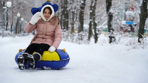 Thumbnail for Young Girl Rolling on Tubing in the Park in Winter