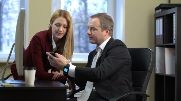 Thumbnail for A Businessman Shows an Attractive Young Woman Smart Watch at the Office