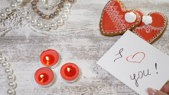 St Valentine Day Background Two Heart Shaped Ginger Biscuits, Tea Candles and Pearl Beads on