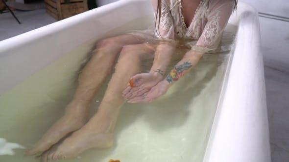 Thumbnail for schlank Mädchen mit einem tätowiert legt in die Badezimmer fängt ein Goldfisch