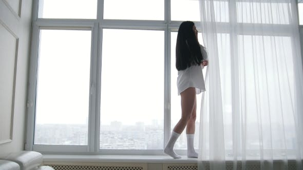 Thumbnail for Beautiful Young Woman in a White Men's Shirt and Socks Walking on Windowsill and Talking on the