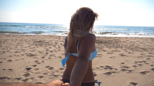 Thumbnail for Follow Me Shot of Young Woman Pull Her Boyfriend To the Sea Shore on Sunny Day
