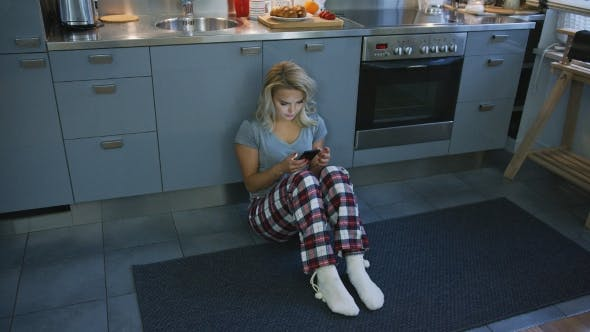 Thumbnail for Lovely Woman Browsing Smartphone on Kitchen Floor