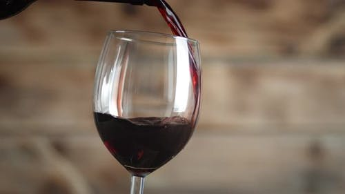 Red Wine Pours Into a Glass. On a Wooden Background. High Quality  Footage