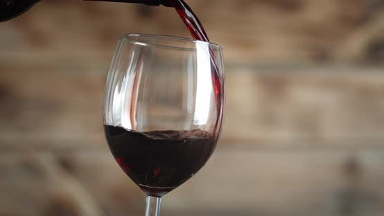 Thumbnail for Red Wine Pours Into a Glass. On a Wooden Background. High Quality  Footage