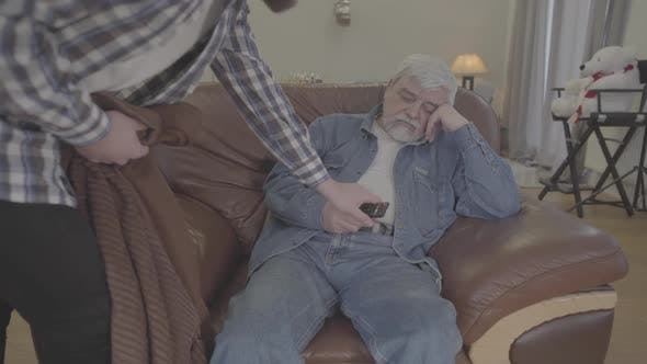 Thumbnail for Portrait of Mature Grey-haired Caucasian Man Sleeping on Armchair with Remote Control As Adult