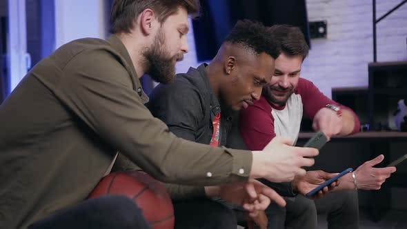 Thumbnail for Young Diverse Guys which Sitting on Sofa and Using their Phones while Watching TV