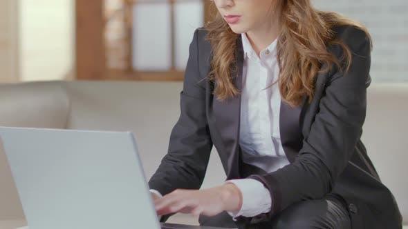 Thumbnail for Geschäftsfrau sitzt auf der Couch und Tippen auf Laptop, Vorbereitung auf das Treffen