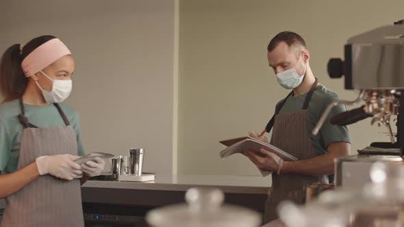 Deux barmen tiennent des registres des paquets de café