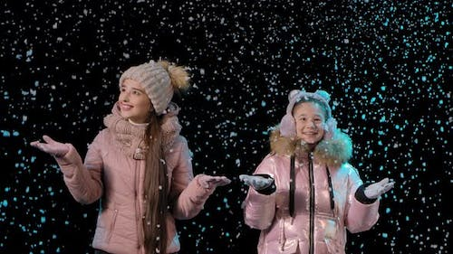 Joyful Mother and Daughter Rejoice at the First Snow. Happy Family in the Studio on a Black