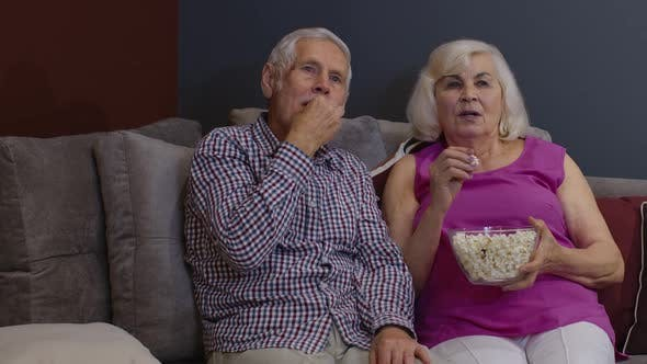 Thumbnail for Scared Senior Old Couple Holding Popcorn Watching Horror Tv Show Film Sitting on Sofa in Living Room