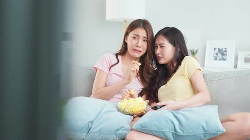 Asian young woman couple watch jump scare movie on television at home.