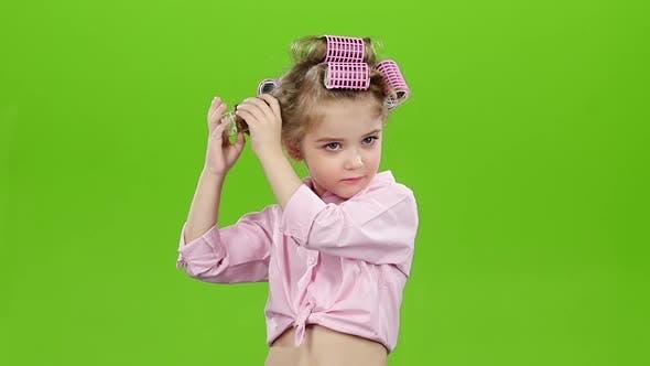 Kleines Mädchen mit Lockenwicklern auf seinem Kopf, entfernt Lockenwickler. Grüner Bildschirm. Zeitlupe